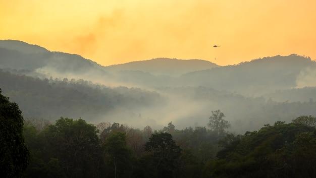Helikopter służb ratunkowych zrzuca wodę, aby ugasić pożary lasów
