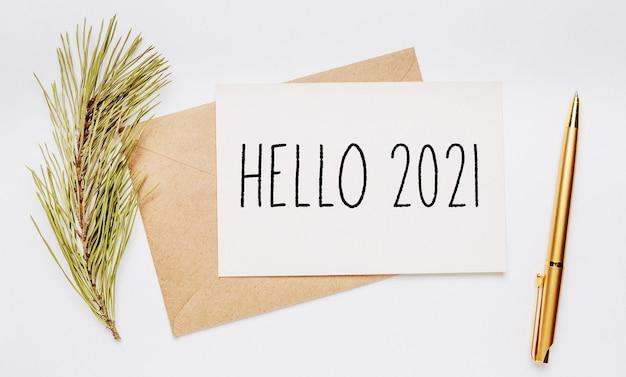 Hello 2021 notatka z kopertą, gałązką świerku i złotym piórem na białej powierzchni. wesołych świąt i nowego roku koncepcja