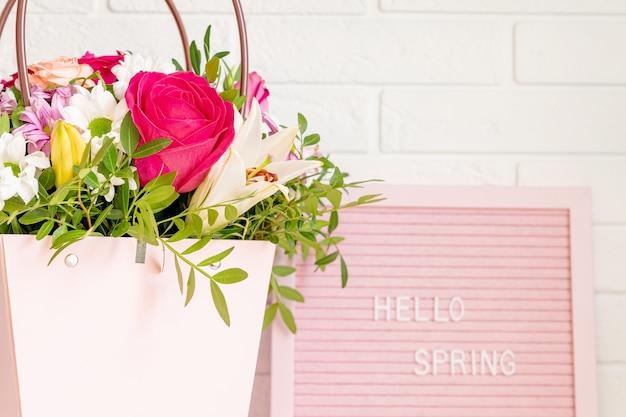 Hello spring - tekst na różowej tablicy filcowej z kwitnącymi kwiatami i zielonymi liśćmi na tle ściany z białej cegły.