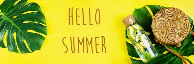 Hello summer banner na stronie internetowej. okrągła torba rattanowa i szklana butelka z lemoniadą i liściem monstera. żółte, słoneczne tło. leżał płasko, widok z góry