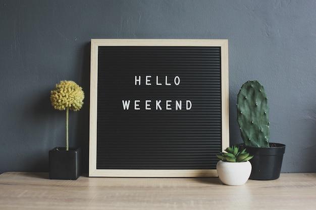 Hello weekend cytat na tablicy z kaktusem, sukulentem i dekoracyjną rośliną na drewnianym stole