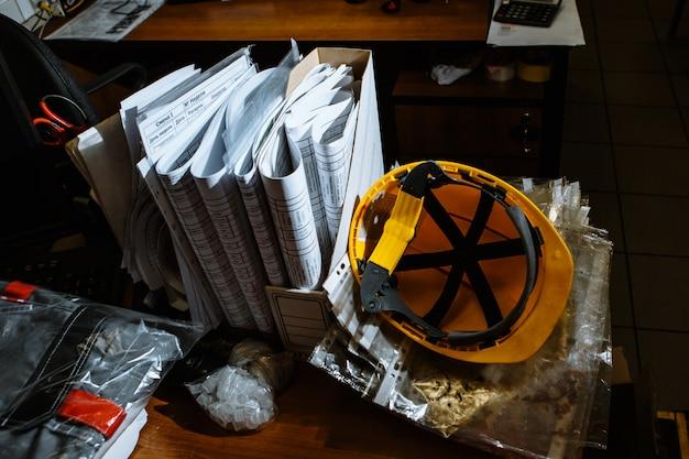 Hełm pracy żółty leżący na stole
