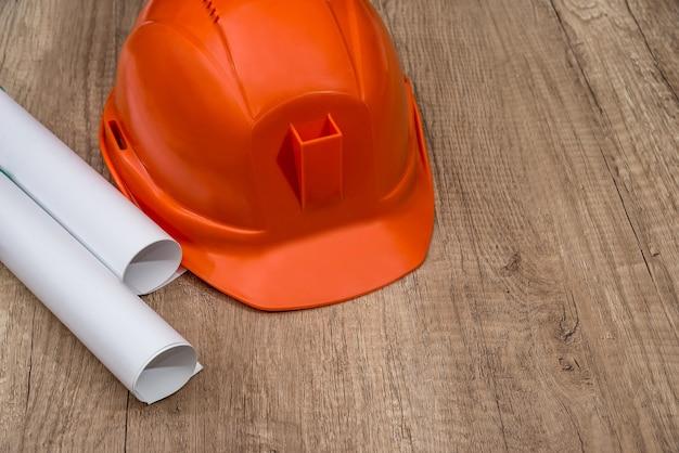 Hełm z rolką papieru budowlanego na drewnianym biurku