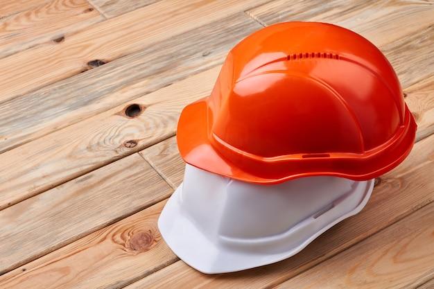 Hełmy ochronne na drewnianym tle. pomarańczowe i białe kaski. zasada numer jeden to bezpieczeństwo.
