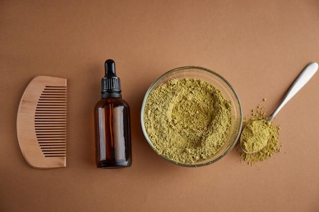 Henna mehndi barwnik w proszku w szklanej misce i drewnianym grzebieniu, widok z góry. ajurwedyczne produkty do pielęgnacji włosów. naturalna pielęgnacja i koloryzacja włosów.