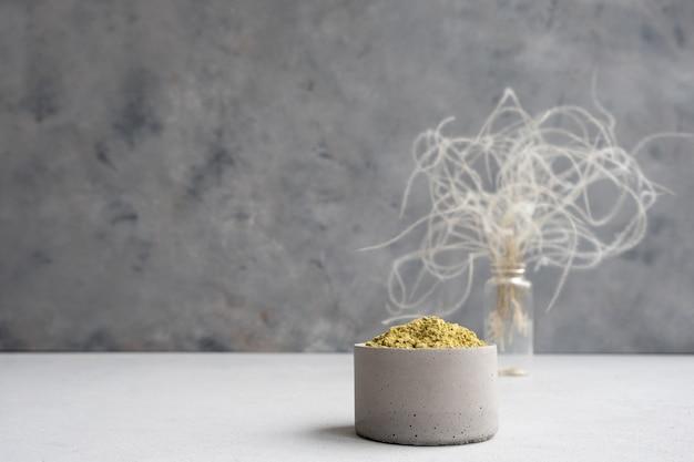 Henna w proszku do farbowania włosów i brwi oraz rysowania mehendi na dłoniach na szarym cementowym postumencie z suszonymi kwiatami lub białym kwiatem.
