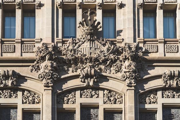 Herb barcelony wyrzeźbiony na fasadzie modernistycznego budynku