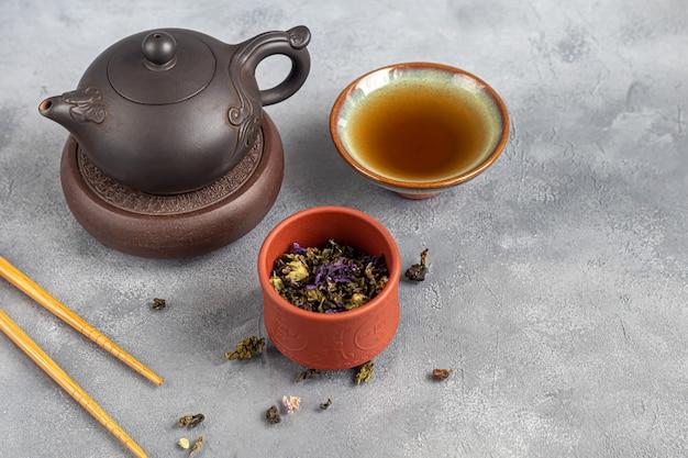 Herbaciana ceremonia. chińskie pu-erh w misce. w tle brązowy imbryk i liście herbaty. skopiuj miejsce.