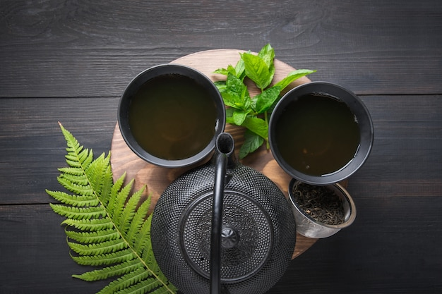 Herbaciana ceremonia. dwa filiżanki herbata z mennicą i czajnikiem na ciemnym tle. koncepcja chińskiej herbaty. widok z góry.