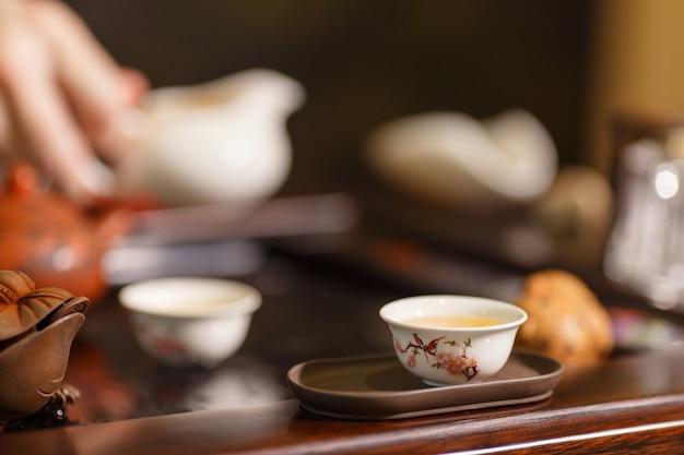 Herbaciana ceremonia. mistrz nalewa herbatę do białych filiżanek.