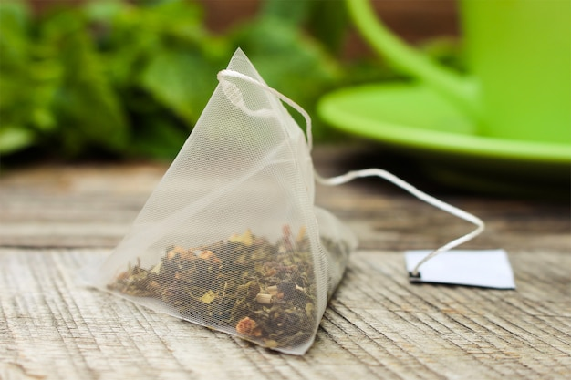 Herbaciana torba na tle mennica i zielona filiżanka i