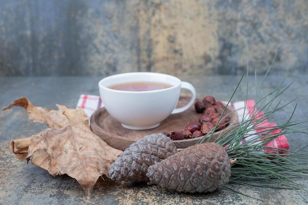 Herbata aromatyczna w białej filiżance z owocami dzikiej róży i szyszkami na marmurowym stole