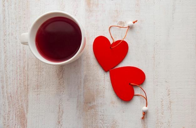 Herbata berberysowa, widok z góry, biały kubek z herbatą, ciepła herbata na śniadanie, dwa czerwone serduszka.