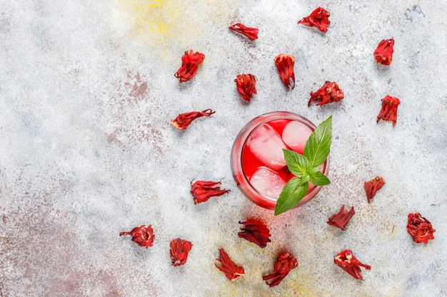 Herbata cold brew z hibiskusem z lodem i liśćmi bazylii.