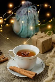 Herbata cynamonowa na stole ozdobionym girlandami i prezentami. przytulny wieczór w domu.