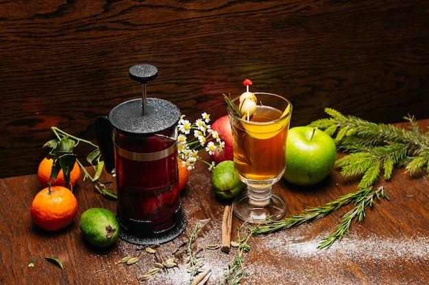 Herbata cytrusowa w prasie francuskiej i herbata cytrusowa w przezroczystym kubku z jabłkiem i liczi na stole w restauracji