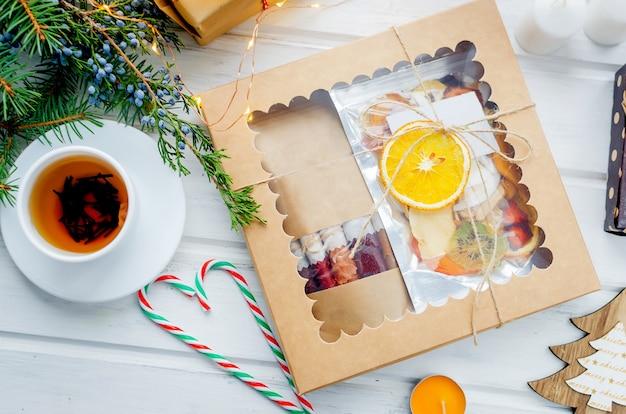 Herbata i pudełko z suchych chipsów owocowych na drewnianym stole