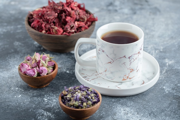 Herbata i suszone kwiaty na marmurowym stole.