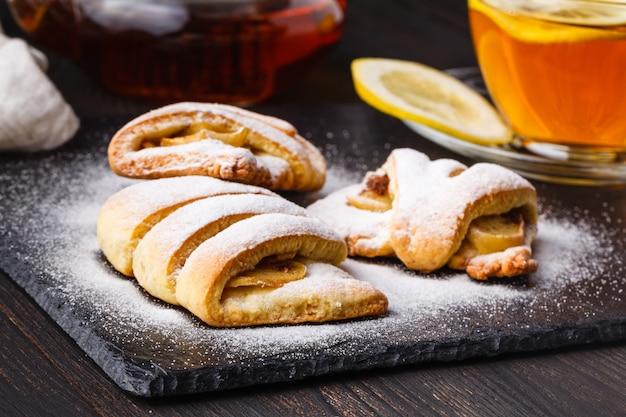 Herbata i świeżo upieczone ciasteczka jabłkowe z twarogiem przyozdobione cukrem