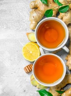 Herbata imbirowa w filiżance i cytryna. na powierzchni rustykalnej
