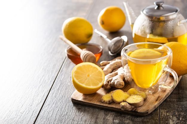 Herbata imbirowa z cytryną i miodem w kryształowym szkle na drewnianym stole