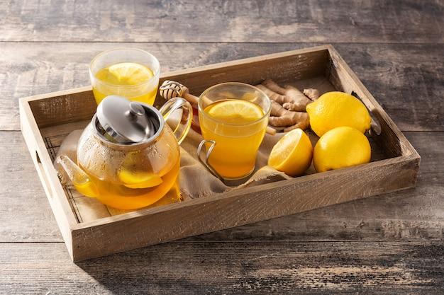 Herbata imbirowa z cytryną i miodem w kryształowym szkle na tacy