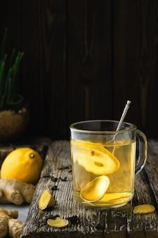 Herbata imbirowa z cytryną w szklance, zbliżenie, składniki na herbatę na drewnianym stole vintage. zapobieganie i wspieranie odporności