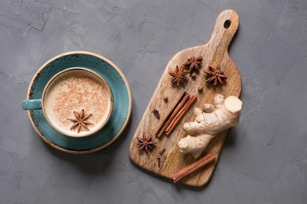 Herbata indyjska masala w filiżance z przyprawami na szarym betonowym stole. widok z góry.