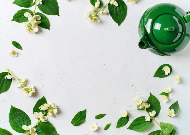 Herbata jaśminowa z imbrykiem, kwiatami i liśćmi na białym tle, miejsce na kopię, widok z góry