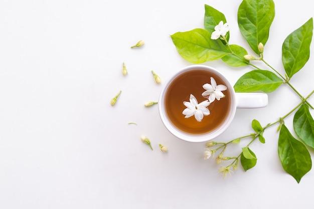 Herbata jaśminowa z kwiatami jaśminu w białej filiżance na białym drewnianym drewnianym stole.