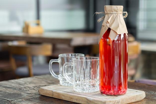 Herbata kombucha z jagodami w szklanej butelce obok szklanych filiżanek. zdrowy napój fermentowany