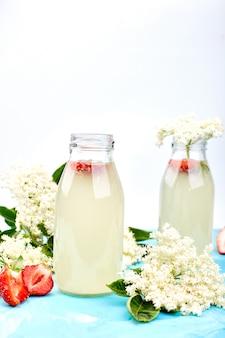 Herbata kombucha ze kwiatem bzu czarnego i truskawką na niebieskiej powierzchni