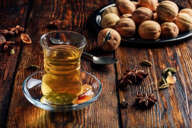 Herbata korzenna z anyżem, kardamonem i suszoną limonką w szkle armudu na drewnianej powierzchni