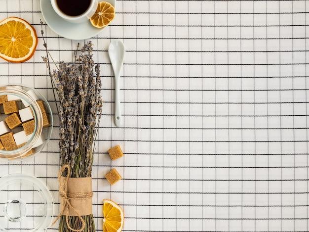 Herbata, lawenda, cukier i plasterki cytryny na białym obrusie w kratkę.