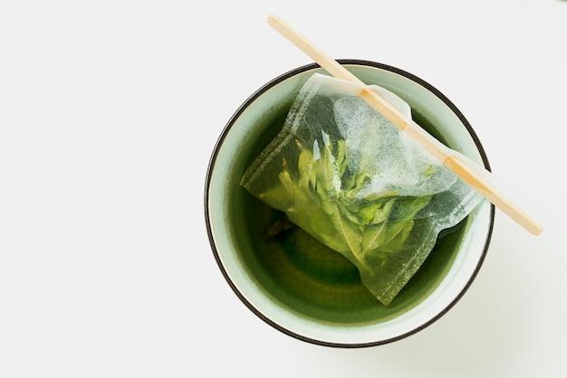 Herbata lemon verbena w kubku z ręcznie robioną torebką na białym biurku. odosobniony. widok z góry. flat lay.