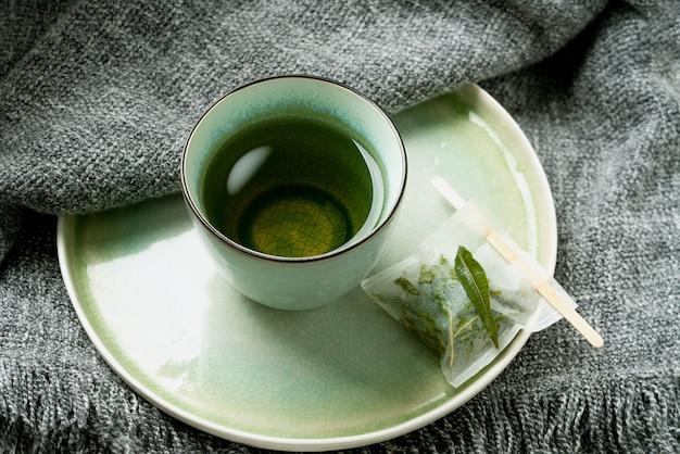 Herbata lemon verbena w kubku z ręcznie robioną torebką na szarym kocu. koncepcja przytulności. ścieśniać.