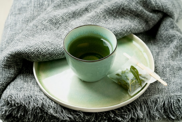 Herbata lemon verbena w kubku z ręcznie robioną torebką na szarym kocu. koncepcja przytulności. selektywna ostrość. ścieśniać.