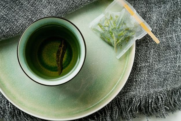 Herbata lemon verbena w kubku z ręcznie robioną torebką na szarym kocu. koncepcja przytulności. widok z góry. flat lay