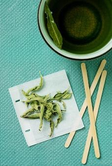 Herbata lemon verbena w kubku z ręcznie robioną torebką na zielonym biurku. widok z góry. flat lay