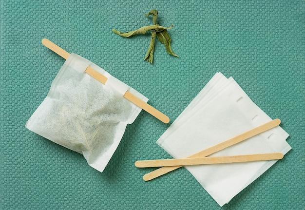 Herbata lemon verbena w ręcznie robionej torebce na zielonym biurku. widok z góry. flat lay
