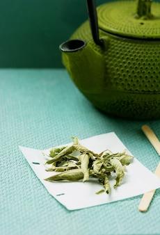 Herbata lemon verbena w ręcznie robionej torebce z imbrykiem na zielonym biurku. selective focus close up