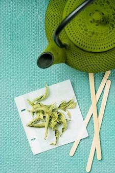 Herbata lemon verbena w ręcznie robionej torebce z zielonym imbrykiem vintage. widok z góry. flat lay