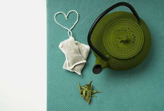Herbata lemon verbena w torebce ze sznurkiem w kształcie serca i czajniczkiem. widok z góry. flat lay