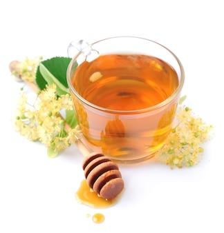 Herbata lipowa z kwiatami i miodem na białym tle