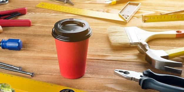 Herbata lub kawa w jednorazowym kubku, narzędzia do profesjonalnej budowy lub naprawy domu, na drewnianym stole. przekąska lub przerwa w miejscu pracy brygadzisty lub cieśli. przyciemniane zdjęcie. transparent.
