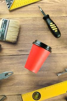 Herbata lub kawa w jednorazowym kubku, narzędzia do profesjonalnej budowy lub naprawy domu, na drewnianym stole.