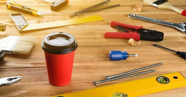 Herbata lub kawa w jednorazowym kubku, narzędzia do profesjonalnej budowy lub naprawy w domu