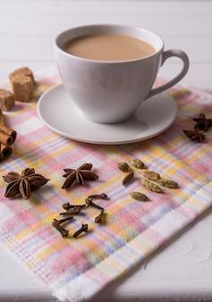 Herbata masala chai w filiżance, brązowy cukier, laski cynamonu, anyż i badian