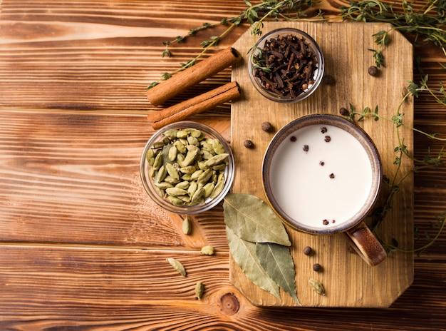 Herbata masala to tradycyjny indyjski napój z mlekiem i przyprawami na drewnianym stole obok składników.