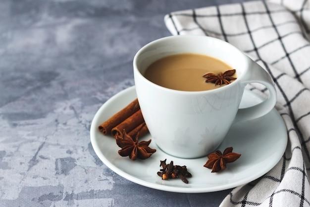 Herbata masala w białej ceramicznej filiżance z przyprawami